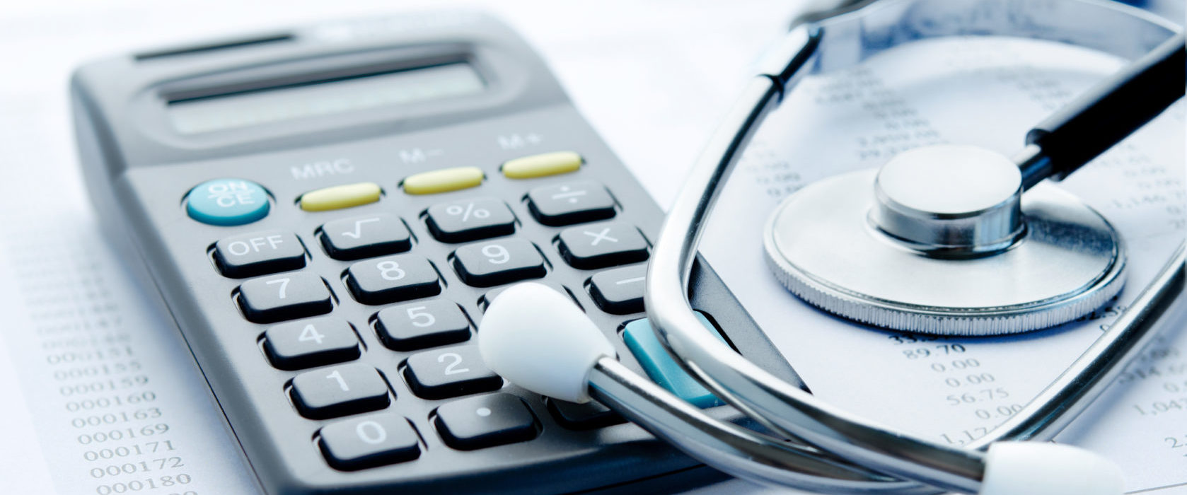 A calculator beside a stethoscope on top of paperwork